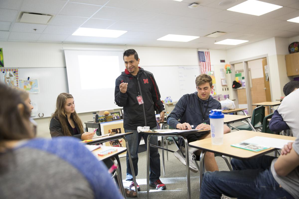 Teenagers sit talking with an instructor in a classroom