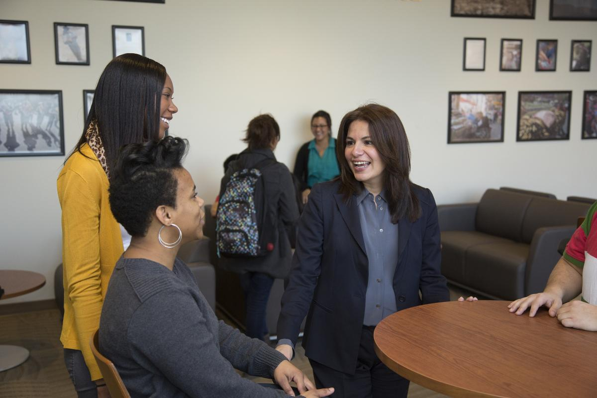 A Latina businesswoman speaks with two other women