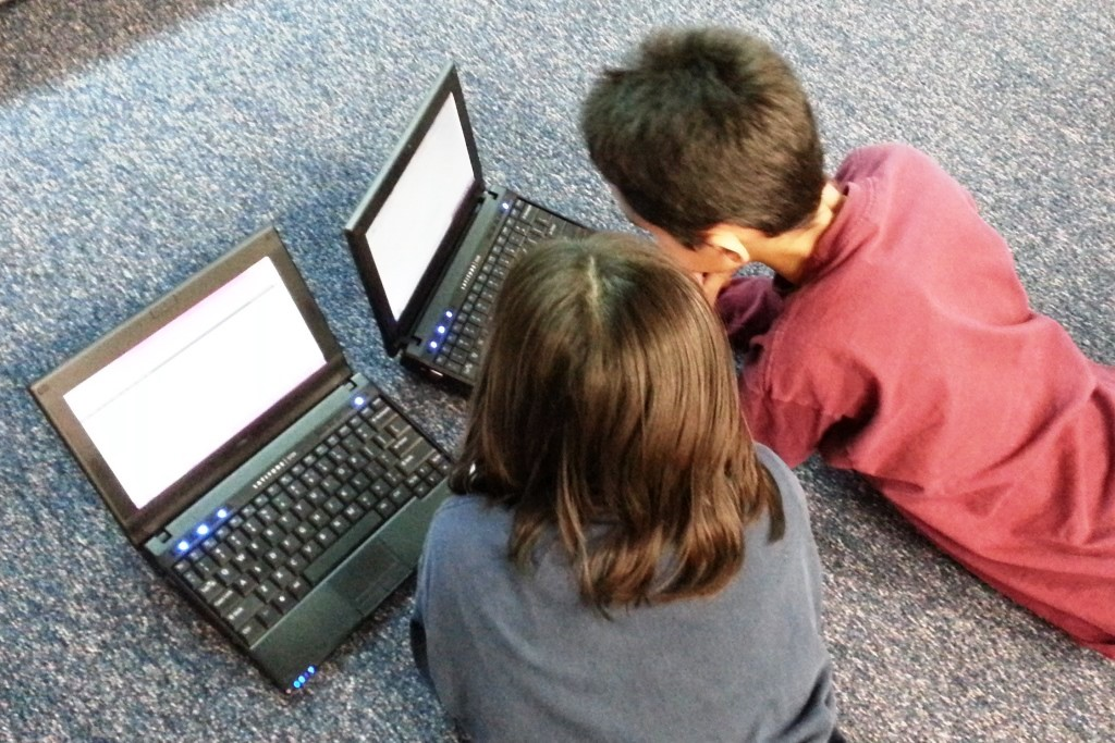 Two children using laptops
