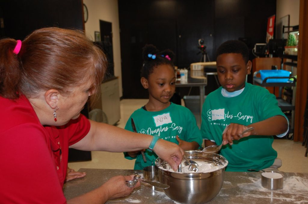staff member instructing clover kids how to measure ingredients